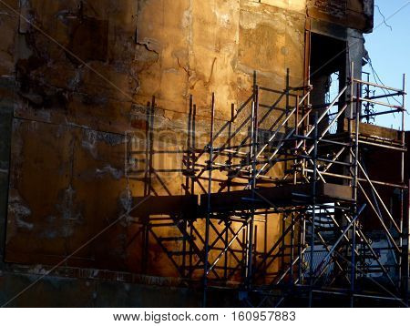 Demolition site scaffolding with shadows at dusk