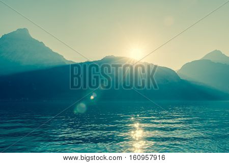 Inspiring panorama of the mountains and lake. The sun sets with bright rays of the tops sun flair