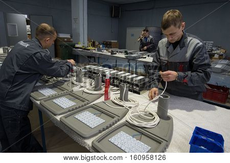 Saint-Petersburg Russia - November 30 2016: Electricians in the shop assembling urban electric lamps. for the production of lighting equipment factory.
