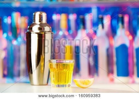 Picture of glass, lemon segment and shaker standing on a bar counter with copy-space