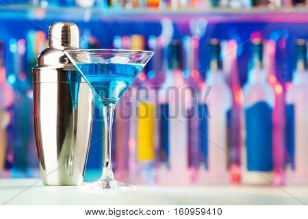 Picture of martini glass filled with blue liquor and shaker standing on a bar counter