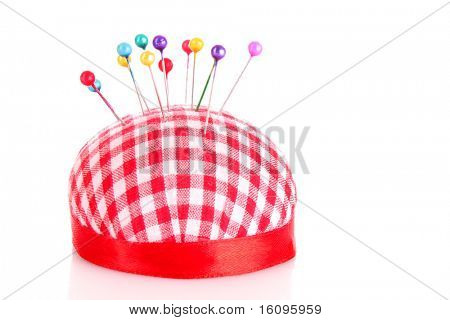 Colored pinheads in pin-cushion isolated on white poster