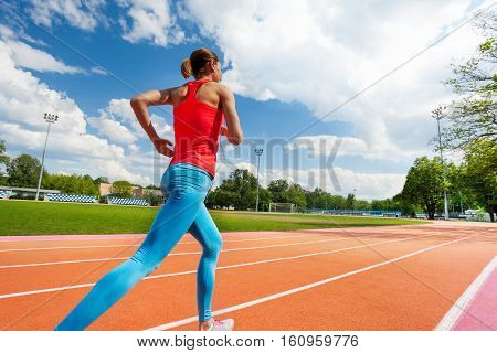 Portrait of athletic woman running on stadiums track in summer, back view