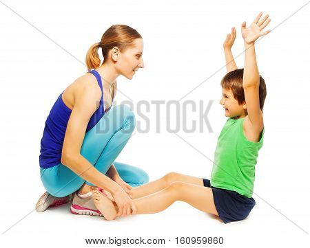 Portrait of young mother helping her happy kid son doing physical exercises, isolated on white