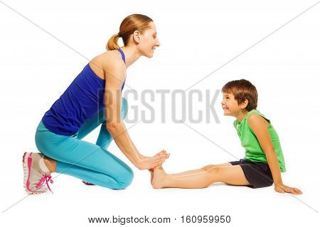 Happy kid boy stretching legs, sitting on the floor with mom, isolated on white