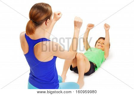 Smiling happy boy doing exercises laying flat on back and raising his hands up with female trainer, isolated on white