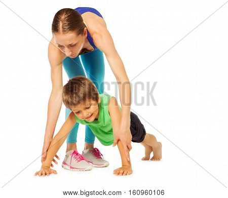 Sporty mother helping her kid son doing pushing ups, isolated on white