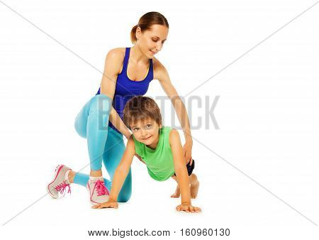 Sporty mother teaching her kid son doing pushing ups, isolated on white