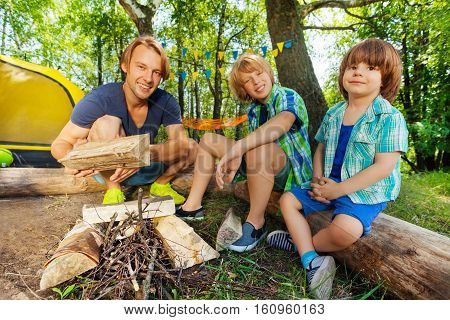 Portrait of happy father teaching his two age-diverse boys making a camp fire, sitting on the logs next to the tent