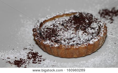 A cream-filled pir with sugar and cocoa powder sprinkled on it.