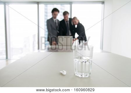 Close up of a glass of water and pills, business people, working all day, court fight, painful business pie sharing, monitoring elections, looking for an error. Business and healthcare concept