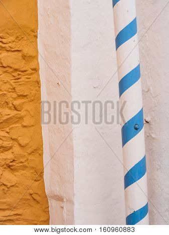 Striped pole detail and yellow wall near the Battery Portmeirion Wales