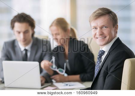 Portrait of businessman with subordinates at the background. Group of business people, friendly smiling middle aged man looking at camera, teamwork concept, conference hall for rent, applicant for job