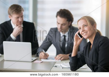 The group of businessmen working at the office desk woman demonstrating impolite office behavior, discussing private things in front of male colleagues, chatty lady, nonstop dialogue with a client