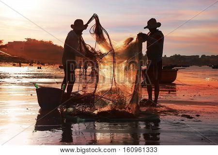 Vietnamese fishermen dismantling fishing nets in the setting sun. Mui Ne Vietnam