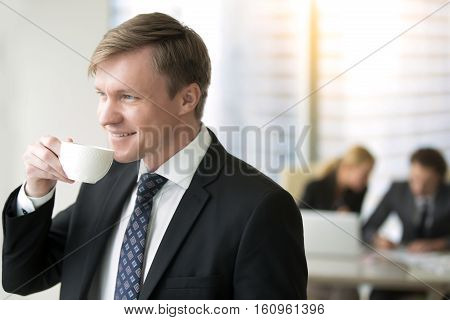 Young smiling businessman drinking tea or coffee, in modern office, dreaming of making fabulous income, look forward to holidays, overcame challenges and having a rest, shift responsibility to others