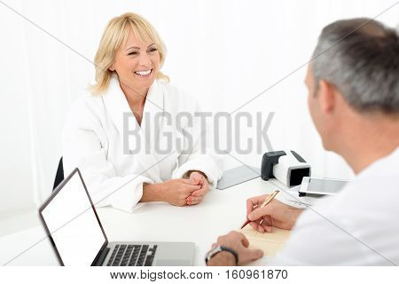 I feel myself great. Happy senior woman is talking with male doctor and smiling. She is sitting in white bathrobe. Man is making notes