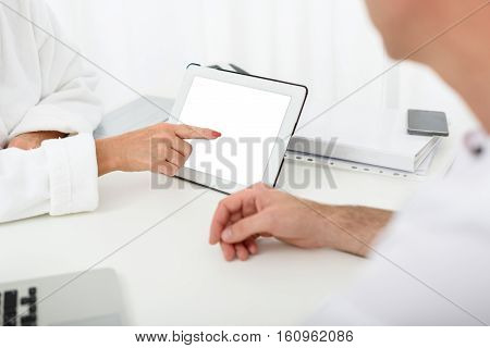 Close up of female hand pointing finger at tablet screen. Woman asking advice in male beautician at beauty salon