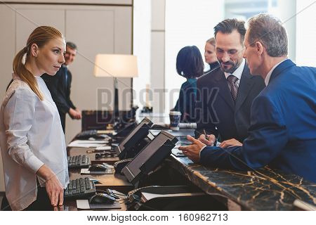 Listening to you carefully. Female receptionist talking to mature businessmen while one smiling man fill in form