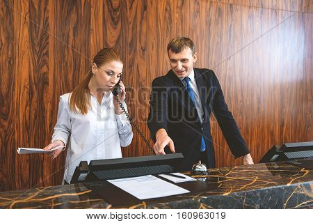Be attentive. Female receptionist talking on phone with customer while male desk clerk pointing fingert at computer screen