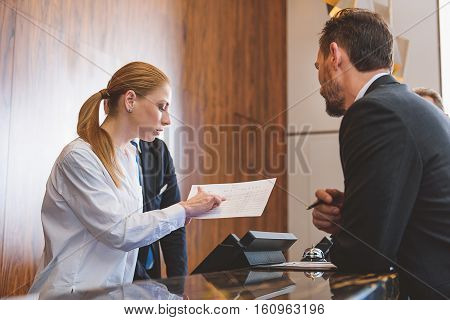Assisting client with pleasure. Young female receptionist helping mature man to check in at hotel while searching for his name in list