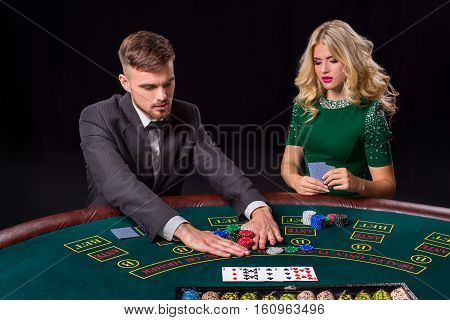 couple playing poker at the green table. The blonde girl and a guy in a suit. all-in bets chips