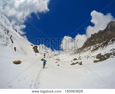 Trekker on the trail in the mountains. Sport girl with backpack travels in Himalayas. Nepal trek to ABC. Female traveler near Annapurna Base Camp. Snow and rocks winter severe landscape for background