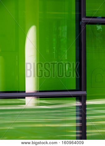 Reflection in a building with green glass demonstrating contemporary architecture and regeneration in Salford Quays near Manchester England.