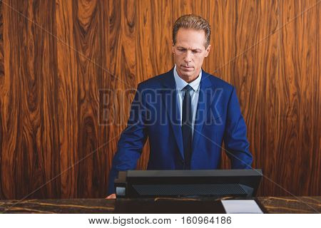 Always monitoring situation. Presentable adult hotel owner attentively looking at computer screen while being behind desk in hall