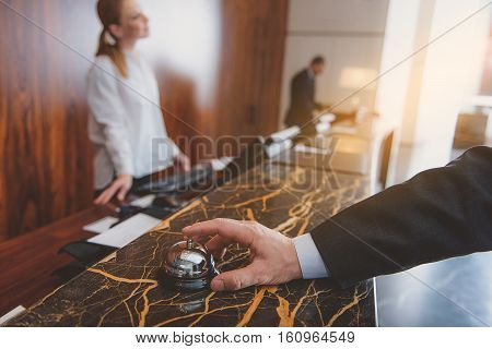Service, please. Close up of male hand ringing at counter with index finger. Female receptionist standing on background