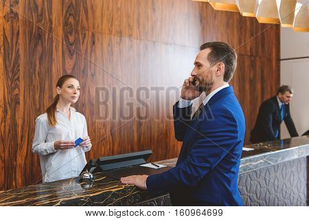 I arrived, everything is fine. Mature businessman talking on smart phone and waiting for registration. Female receptionist holding cardkey and looking at him