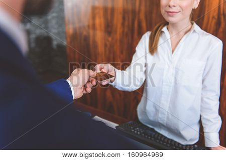 Never go out without it. Close up of man handing over his credit card to woman at reception