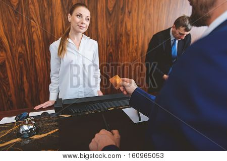 Yes, we do accept credit cards. Businessman paying for his services with credit card in hotel while female attractive receptionist looking at him