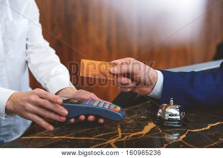 Payments are made easy. Close up of male customer paying to hotel manager by credit card at reception