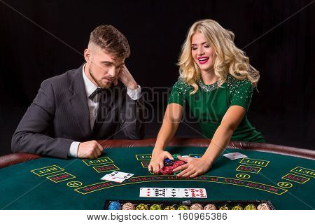 couple playing poker at the green table. The blonde girl and a guy in a suit. happy win