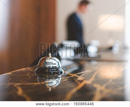 Close up of modern luxury hotel counter desk with bell and male employee on background