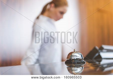 We are ready to receive guests. Close up of service chrome bell in hotel with female receptionist standing on background