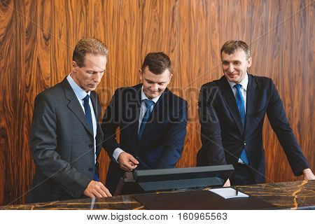 Completely ready to work. Supervisor with hotel staff standing at desk and having meeting while looking at computer screen