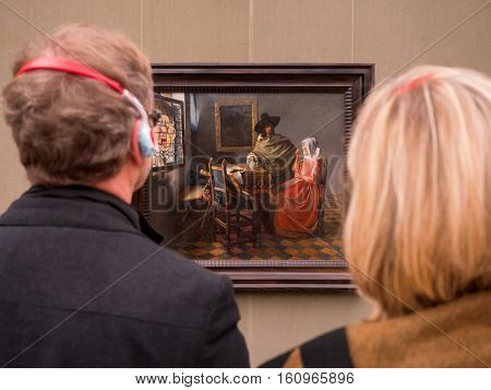 Tourists Admire A Paint In A Gallery