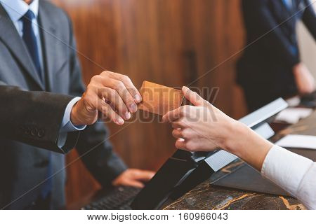 Swipe it off my business account. Close up of woman handing over her credit card to manager at reception desk