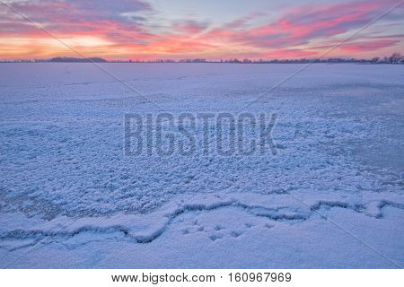 Ice and snow cover a lake at sunrise