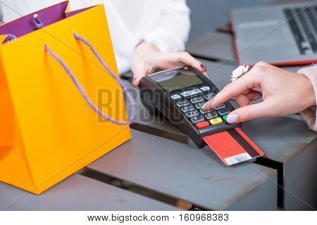 Entering pin code on the banking terminal at the store