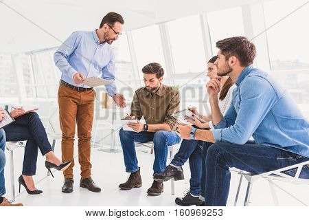 Group of people are on psychological training. They listen carefully to master