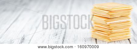 Portion Of Cheese Slices On Wooden Background (selective Focus)