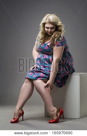 Young beautiful blonde plus size model in red high heels shoes xxl woman on gray studio background legs fatigue