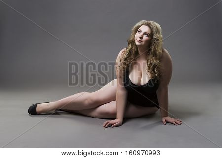 Young beautiful blonde plus size model with big natural breasts in underwear xxl woman on gray studio background full length portrait