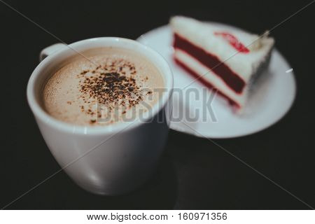 Vintage film look of cappuccino coffee and red velvet cake.