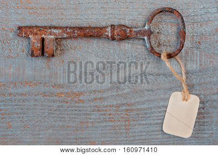 Old key with a paper label lies on a wooden board