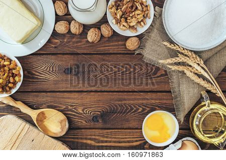 Christmas and holiday baking background, flour, bakeware, walnuts, milk, butter, eggs and sugar on a wooden board, viewed from above. top view. culinary concept