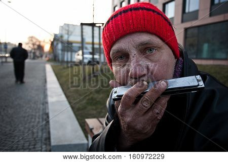Old Homeless man playing harmonica. Czech Republic 06.11.2014